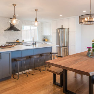 Mid-sized transitional medium tone wood floor and brown floor kitchen/dining room combo photo in Denver with white walls