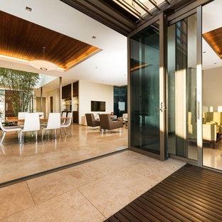 Foto di una sala da pranzo aperta verso il soggiorno design con pareti bianche, pavimento in marmo, camino sospeso, cornice del camino in legno e pavimento beige