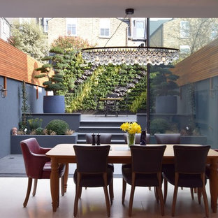 Medium sized modern dining room in London with white walls.