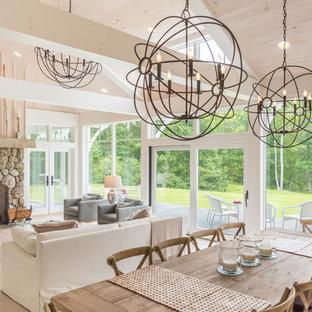 Diseño de comedor rústico, grande, abierto, con paredes beige, suelo de madera clara, chimenea tradicional, marco de chimenea de piedra y suelo beige