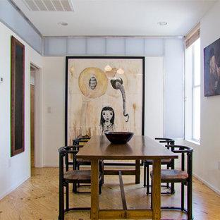 Imagen de comedor actual, pequeño, abierto, con paredes blancas y suelo de contrachapado