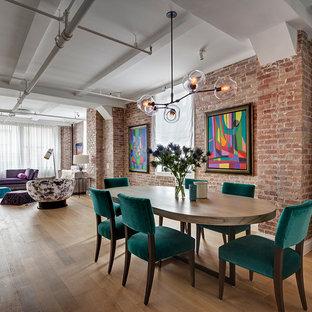 Foto di una sala da pranzo aperta verso il soggiorno industriale con parquet chiaro e nessun camino