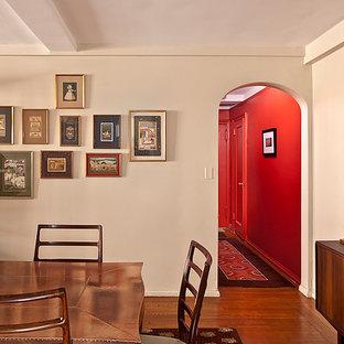 ニューヨークの中くらいのミッドセンチュリースタイルのおしゃれな独立型ダイニング (白い壁、濃色無垢フローリング、標準型暖炉、レンガの暖炉まわり) の写真