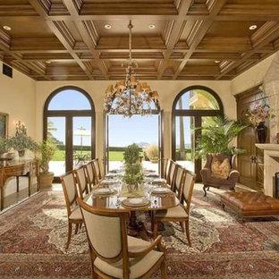 Esempio di un'ampia sala da pranzo aperta verso il soggiorno mediterranea con pareti beige, camino classico, cornice del camino in pietra, pavimento in marmo e pavimento marrone