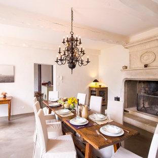 Idées déco pour une grande salle à manger campagne fermée avec un mur blanc, béton au sol, une cheminée standard et un manteau de cheminée en pierre.