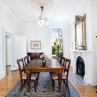 Immagine di una sala da pranzo chic chiusa con pareti bianche, pavimento in legno massello medio, camino classico, cornice del camino in intonaco e pavimento marrone