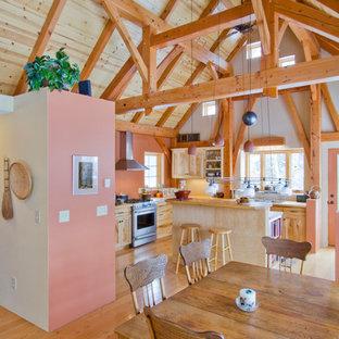 Inspiration för mellanstora lantliga matplatser med öppen planlösning, med rosa väggar och mellanmörkt trägolv