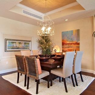 Foto di una sala da pranzo aperta verso la cucina tropicale di medie dimensioni con pareti beige, pavimento in laminato, nessun camino e pavimento marrone