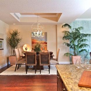 Immagine di una sala da pranzo aperta verso la cucina tropicale di medie dimensioni con pareti beige, pavimento in laminato, nessun camino e pavimento marrone
