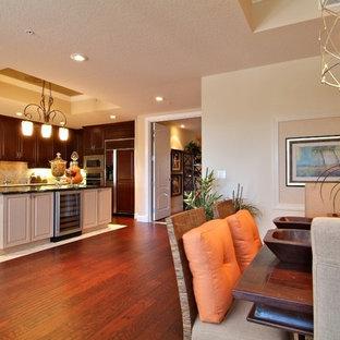 Ispirazione per una sala da pranzo aperta verso la cucina tropicale di medie dimensioni con pareti beige, pavimento in laminato, nessun camino e pavimento marrone