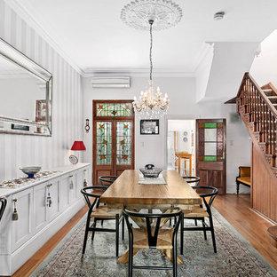 Victorian separate dining room in Sydney with white walls, medium hardwood floors, no fireplace and brown floor.