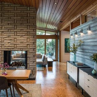 Immagine di una sala da pranzo aperta verso la cucina design di medie dimensioni con pareti grigie, pavimento in bambù, camino bifacciale, cornice del camino in pietra e pavimento beige