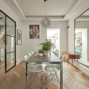Immagine di una sala da pranzo design di medie dimensioni e chiusa con pareti bianche, pavimento in legno massello medio e pavimento marrone