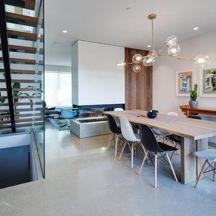 Diseño de comedor de cocina contemporáneo, de tamaño medio, con paredes blancas, suelo de cemento, chimenea de doble cara, suelo gris y marco de chimenea de hormigón