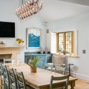 Photo of a large classic kitchen/dining room in Gloucestershire with blue walls, limestone flooring, a wood burning stove, a stone fireplace surround and brown floors.