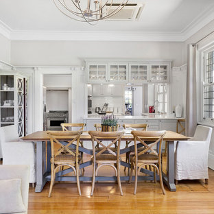 Inspiration for a mid-sized country open plan dining in Wollongong with white walls, light hardwood floors, no fireplace and beige floor.