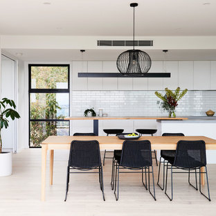 This is an example of a mid-sized modern open plan dining in Geelong with white walls, light hardwood floors and brown floor.