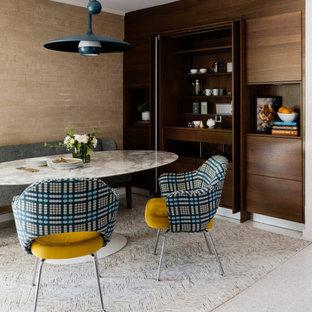 Mittelgroßes Retro Esszimmer ohne Kamin mit beiger Wandfarbe, grauem Boden und Ziegelwänden in Houston