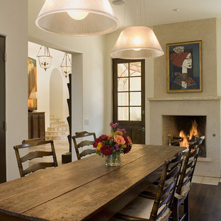 Inspiration for a rustic dark wood floor dining room remodel in Austin with white walls and a standard fireplace