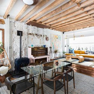 Foto di una sala da pranzo bohémian con pareti bianche, pavimento in legno massello medio, stufa a legna e pavimento marrone