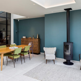 Inspiration for a contemporary open plan dining room in London with blue walls, a wood burning stove, a metal fireplace surround and grey floors.
