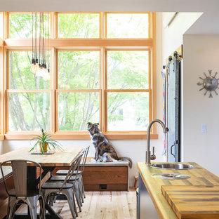 Idee per una piccola sala da pranzo aperta verso la cucina industriale con pareti bianche, parquet chiaro e nessun camino
