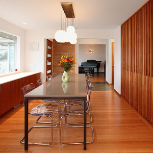 Photo of a midcentury kitchen/dining combo in Seattle with white walls and medium hardwood floors.
