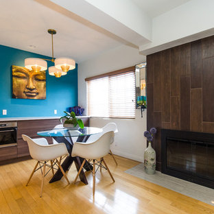 Inspiration for a contemporary medium tone wood floor kitchen/dining room combo remodel in Los Angeles with blue walls, a standard fireplace and a wood fireplace surround