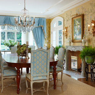 This is an example of a traditional dining room in Detroit with yellow walls and a standard fireplace.