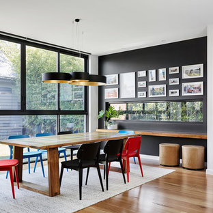 Inspiration for a contemporary dining room in Melbourne with black walls, light hardwood floors and beige floor.