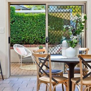 Idée de décoration pour une petit salle à manger ouverte sur le salon tradition avec un mur beige, un sol en carrelage de céramique et un sol rose.