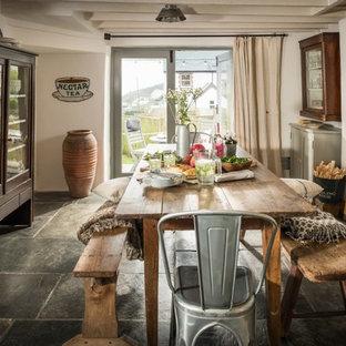 Ejemplo de comedor de cocina rural, de tamaño medio, con paredes blancas, suelo de piedra caliza y suelo gris