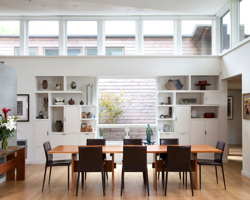 Example Of A Minimalist Dining Room Design In Austin With White Walls And Medium Tone Wood