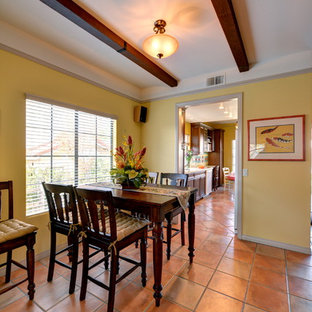 Example of a tuscan terra-cotta floor and pink floor dining room design in San Diego with yellow walls