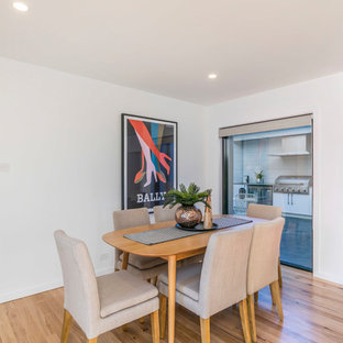 This is an example of a contemporary dining room in Canberra - Queanbeyan with white walls, light hardwood floors and beige floor.