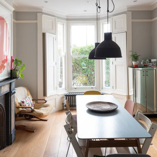Design ideas for a medium sized scandi open plan dining room in London with grey walls, light hardwood flooring, a standard fireplace, a stone fireplace surround and brown floors.