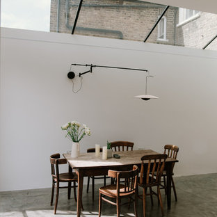Medium sized industrial dining room in London with white walls, concrete flooring and grey floors.