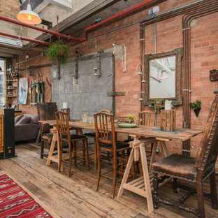 Design ideas for an industrial dining room in London with red walls, medium hardwood flooring and brown floors.
