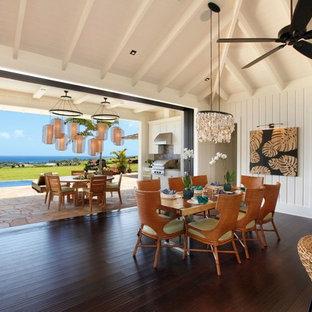 Immagine di una sala da pranzo aperta verso il soggiorno stile marino di medie dimensioni con pareti bianche, pavimento in bambù, pavimento nero e nessun camino