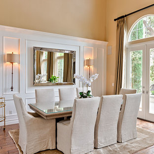 Example of a classic dark wood floor and brown floor dining room design in Los Angeles with yellow walls