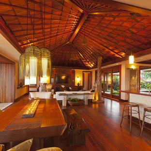 Immagine di una grande sala da pranzo aperta verso il soggiorno tropicale con pareti beige, pavimento in legno massello medio e nessun camino
