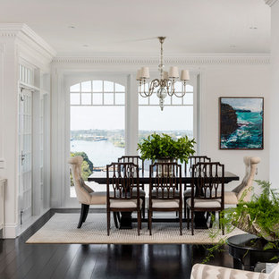 This is an example of a traditional open plan dining in Brisbane with white walls, dark hardwood floors and black floor.