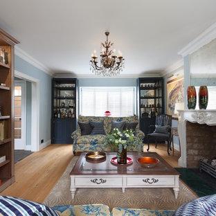 Diseño de comedor contemporáneo, grande, cerrado, con paredes azules, suelo de madera clara, chimenea tradicional, marco de chimenea de yeso y suelo beige