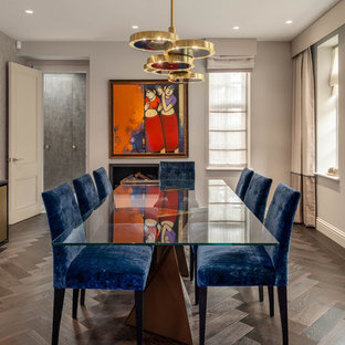 Inspiration for a medium sized classic enclosed dining room in London with grey walls, dark hardwood flooring, a hanging fireplace and brown floors.