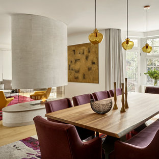 Contemporary open plan dining room in London with light hardwood flooring and a two-sided fireplace.