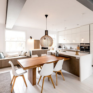 This is an example of a contemporary kitchen/dining room in London with white walls, painted wood flooring and white floors.
