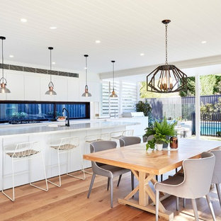Inspiration for a transitional dining room in Newcastle - Maitland with white walls, medium hardwood floors and brown floor.