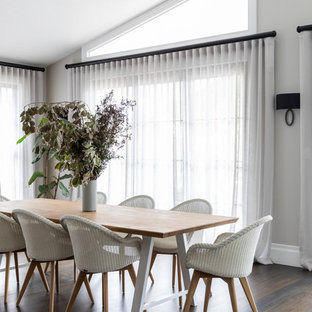 Inspiration for a transitional dining room in Sydney with grey walls, medium hardwood floors and brown floor.