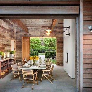 Inspiration for a rustic dining room in New York with a ribbon fireplace.