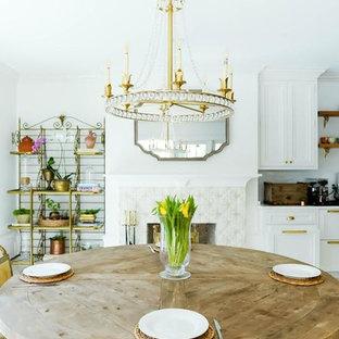 タンパの大きいトラディショナルスタイルのおしゃれなダイニングキッチン (白い壁、大理石の床、標準型暖炉、タイルの暖炉まわり、白い床) の写真